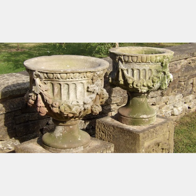 Side view of pair of antique stone urns