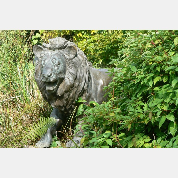 Bronze lion in bushes